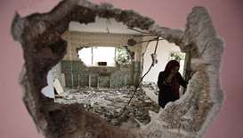 A woman checks the remains of the house of a Palestinian man, who killed three Jewish residents of a