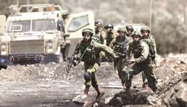 Israeli soldiers charge towards  Palestinian protesters in the West Bank village of Kofr Qadom near