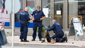 The suspect lies on the ground surrounded by police officers  in Turku