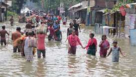 Indian residents wade through flood waters in Balurghat in West Bengal