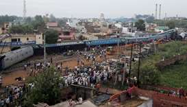 Rescue workers and onlookers stand next to derailed coaches of a passenger train in Khatauli