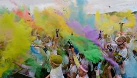 People throw natural coloured powders as the seasons change from winter to spring.