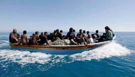 Migrants ride in a boat after they were rescued by Libyan coastguard off the coast of Gharaboli, eas
