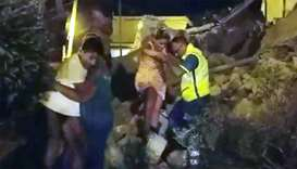 A woman is helped out of debris and rubble after an earthquake hit the island of Ischia