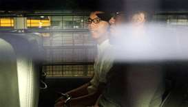 Democracy leader Joshua Wong sits in a prison van as he arrives at the High Court in Hong Kong