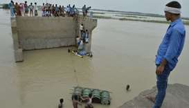 villagers attempting to cross flood waters with the help of rope and empty canisters next to a washe