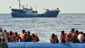 Migrants and refugees sitting on a rubber boat as the Libyan coastguards patrol help them during a r