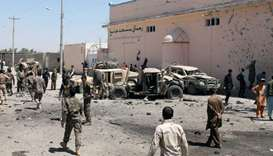 Soldiers inspect damaged army vehicles after a suicide attack in Lashkar Gah, Afghanistan