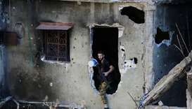 A Palestinian Fatah fighter walks through a hole in a wall inside the  refugee camp near Sidon, sout
