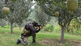 An Indian army soldier stands guard while a gunfight takes place between militants and government fo