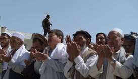 A security guard keeps watch as Afghan mourners and relatives pray in front of the coffin of one of