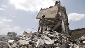Yemeni soldier stands on the debris of a house, hit in an air strike on a residential district in Sa