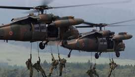 Japanese Ground Self-Defense Force soldiers rappel from UH-60 Black Hawk helicopters during an annua