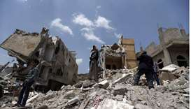 Yemeni men stand on the debris of a house, hit in an air strike on a residential district, in the ca