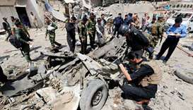 Iraqi security forces inspect the site of a car bomb attack in Jamila market in Sadr City district o