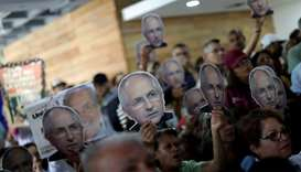 People hold portraits of opposition leader Ledezma during a news conference