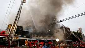 Firefighters operate at the fire site at Tokyo's Tsukiji fish market in Tokyo
