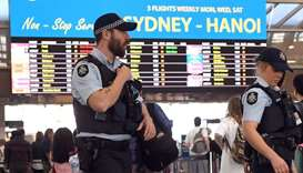 Police walking past passengers as they patrol Sydney Airport