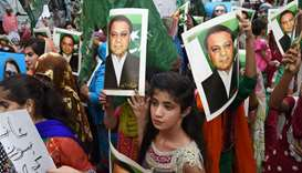Supporters of ousted Pakistani Prime Minister Nawaz Sharif carry placards featuring his images durin