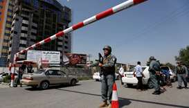 An Afghan police officer inspects vehicles at a checkpoint in Kabul, Afghanistan