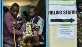 Kenya's Withira Wainana 81-years-old, is assisted after voting