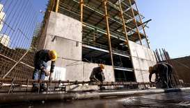 Labourers work at the construction site of a building