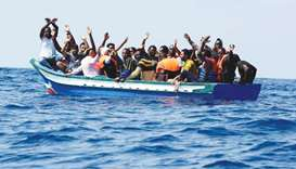 Migrants on a wooden boat react as they wait to be rescued by crew of the Aquarius, in the Mediterra