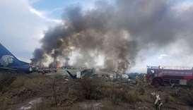 Firefighters douse a fire as smoke billows above the site where an Aeromexico-operated Embraer passe