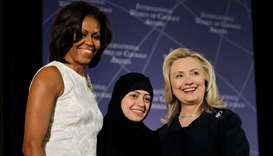 US Secretary of State Hillary Clinton and First lady Michelle Obama (L) congratulate Samar Badawi