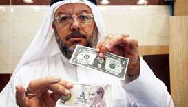 A Kuwaiti man holds a one US dollar bill next to a five Turkish lira banknote at a currency exchange