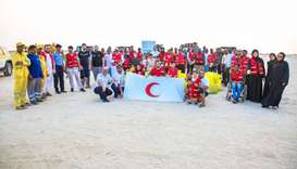 QRCS volunteers pose for a group photograph after cleaning the Eraida beach on the occasion of Inter