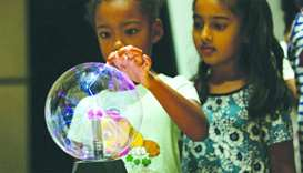 A Summer of Learning participant learns about static electricity using a plasma ball