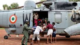 People help a woman disembark from an Indian Navy helicopter at a relief camp after being rescued fr