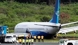 Workers trying to remove the Xiamen Air Boeing 737-800 from the tarmac after it skidded off at the r