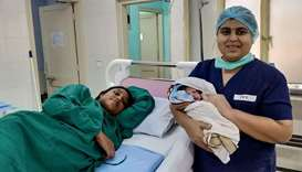 An Indian nurse holding a newborn boy next to the mother Sajita Jabeel (L), 25, in a hospital in Koc