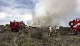Durango's Civil Protection showing firemen working as smoke billows from the wreckage of a plane tha