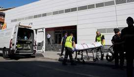 The body of a man who tried to attack a police station is wheeled into a van in Cornella