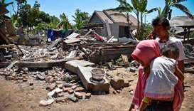 A woman carries her child as they make their way pass collapsed homes in the village of Sugar on Ind