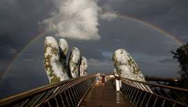 A double rainbow appears above giant hands structure on the Gold Bridge on Ba Na hill near Danang ci