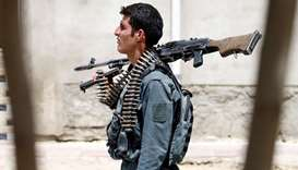 An Afghan policeman keeps watch during a battle with insurgents in Kabul, Afghanistan on August 16,