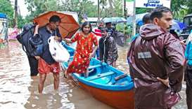 Fishermen and rescue personnel evacuate local residents in a boat in a residential area at Kozhikode