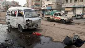 People walk past damaged cars at the entrance of Al-Thawra hospital after an air strike in the Red S