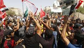 Iraqis shout slogans during ongoing protests in the southern city of Basra