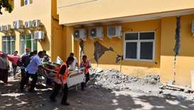 A man is wheeled passed a damaged wall to a makeshift ward set up outside the Moh. Ruslan hospital i