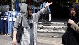 Two Iranian women talk on the street in a shopping district in central Tehran