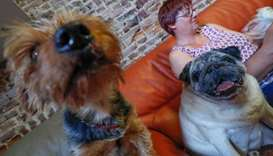Belgian Valerie Luycx, founder of the home, sits with pets