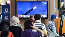People watch a television news screen showing file footage of North Korea's missile launch, at a rai
