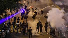 A protester uses a laser pointer as tear gas is fired by police in the Tai Wai area of Hong Kong as