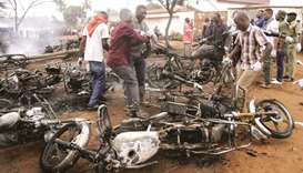 Rescuers remove burnt motorbikes from the scene where a fuel tanker exploded killing a crowd of peop