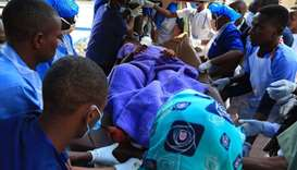 Tanzanian health workers carry a wounded man from a military helicopter at Jangwani, in Dar es Salaa